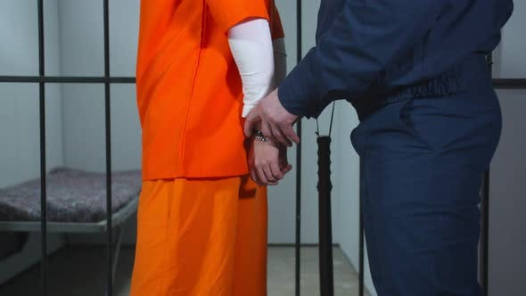 The Guard Removes the Handcuffs From the Prisoner. Close Up