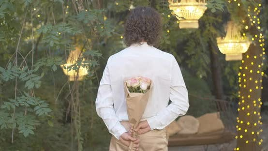 Thumbnail for Back View of Young Man Standing in Summer Evening with Bouquet of Flowers. Elegant Caucasian