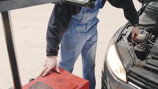 Nahaufnahme von Mechaniker ist das Einstellen von Scheinwerfern. Abblendlicht, Fernlicht. Autoservice.