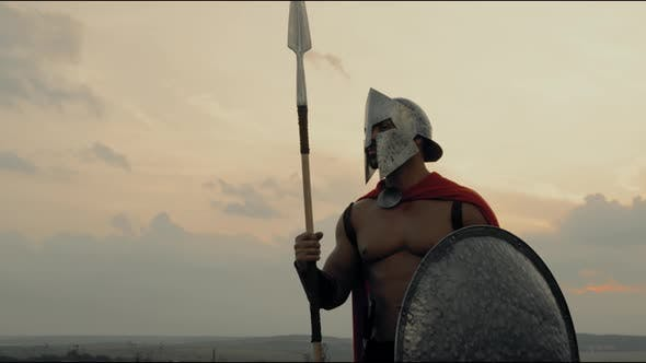 Shirtless Spartan Posing with Spear in Field.
