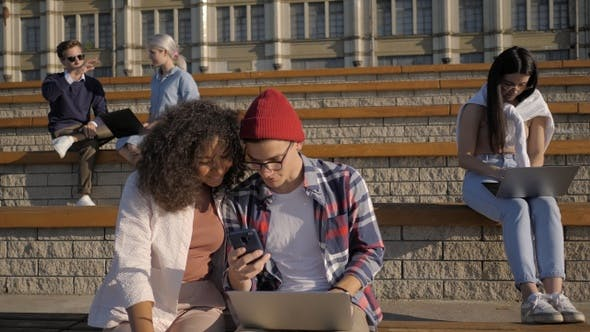 Cover Image for Beautiful couple uses the phone on a bench near college.