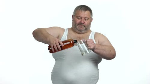 Fat Man Pours Beer From Bottle Into a Beer Glass