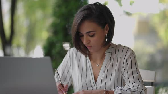 Student Woman Brunette Arabic Hispanic Ethnos Studying Remotely Via the Internet While Sitting in a