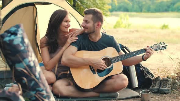 Young Couple with Guitar in Tent