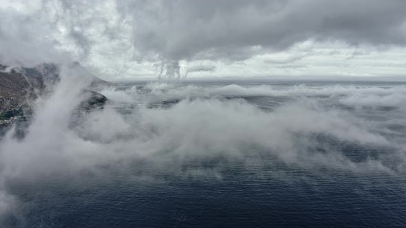 Thumbnail for Slowmo Drone Shot of Deep Blue Seas and Mountain Behind Fog