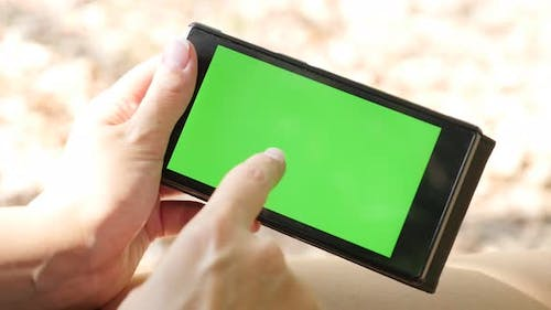 Female using smart phone with green screen display outdoor close-up 4K 2160p UltraHD footage - Woman