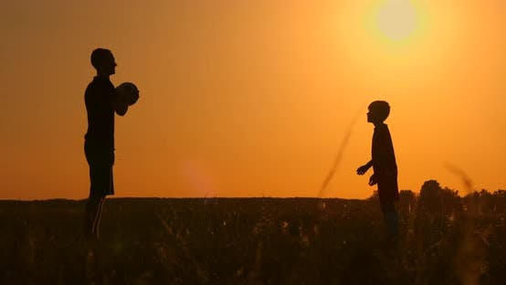 Cover Image for Father and Son Playing Football in the Park at Sunset, Silhouettes Against the Backdrop of a Bright
