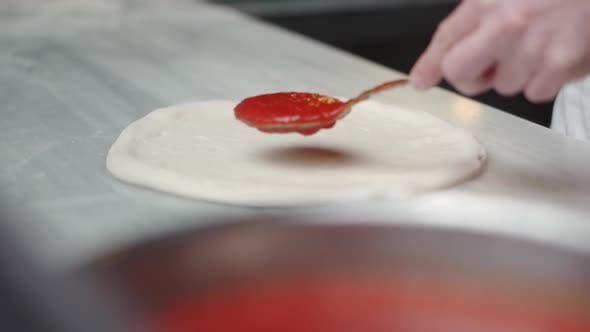 Thumbnail for Spreading Tomato Sauce on Pizza Dough in Pizza Restaurant