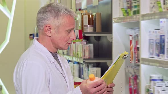 Thumbnail for Senior Pharmacist Working, Reading Papers and Examining Medication