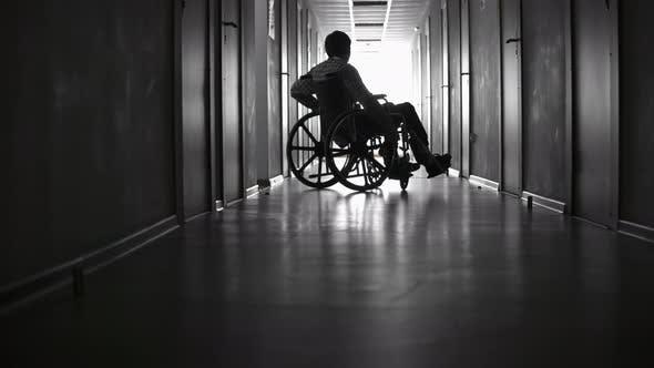 Thumbnail for Disabled Man Riding Wheelchair along Hallway
