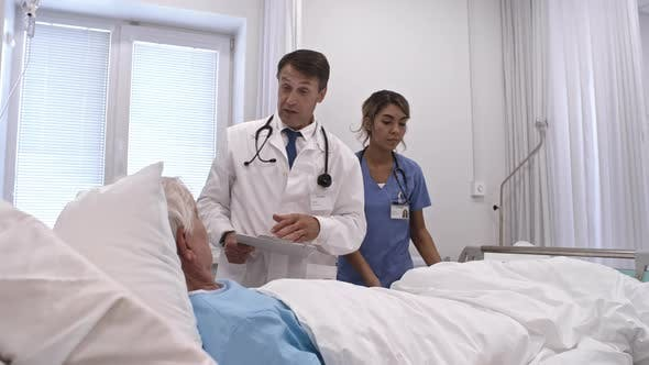 Doctor Consulting Senior Patient in Comfortable Private Ward
