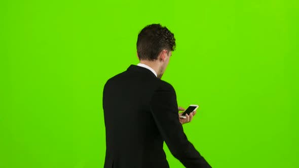 Thumbnail for Man Is a Telephone Rings To Him and He Talks. Green Screen. Back View