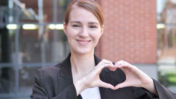 Handmade Heart by Young Businessman Standing Outdoor