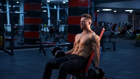 Bodybuilding Stark sitzende Mann trainiert mit Hanteln.