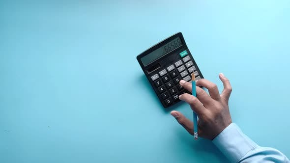 Thumbnail for Top View of Man Hand Using Calculator on Blue Background