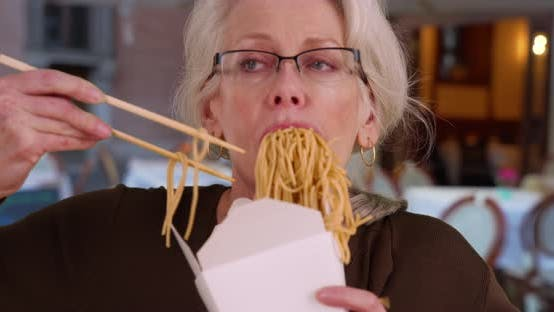 Thumbnail for Mature businesswoman eating Chinese takeaway