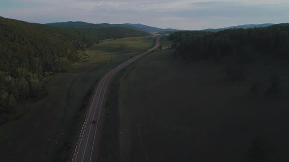 AERIAL, TOP DOWN: Dark Colored Car Driving Down an Asphalt Road Crossing the Vast Forest on a Sunny