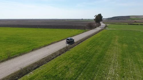 Car Drives on The Road Between Green and Brown Fields