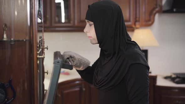 Thumbnail for Side View of Young Muslim Woman in Black Hijab Opening Oven and Smelling Baked Foods. Satisfied