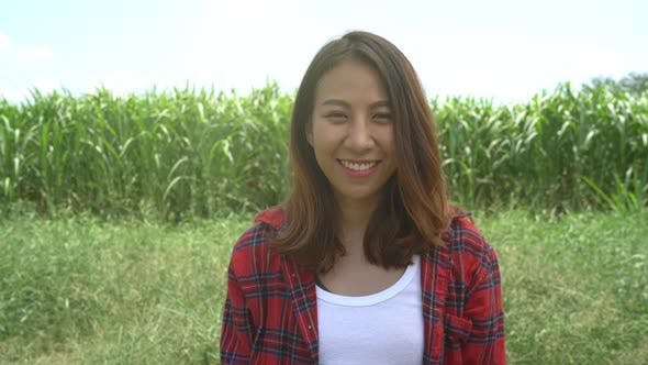 Asian female farmer posing in the corn crop and smiling at camera, agriculture and cultivation.