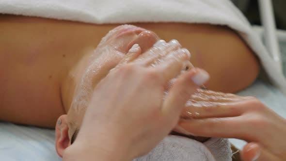 Patientin genießt entspannende Gesichtsmassage im Kosmetologie-Spa-Zentrum