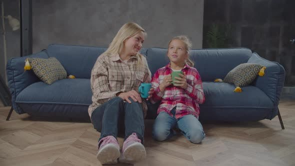 Thumbnail for Positive Mom and Cute Daughter Drinking Tea Indoor