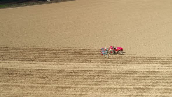 a Redder Tractor Plows a Field