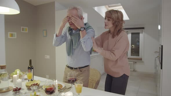 Senior Woman Surprising Husband by Holiday Dinner and Present