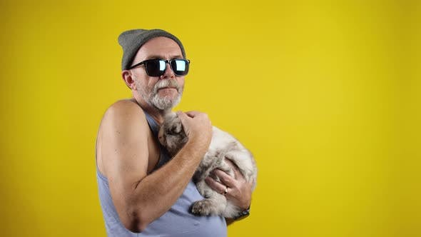 Mature hipster man with a bunny on hands.