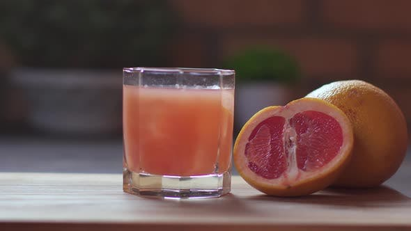 Thumbnail for Close-up of Unrecognizable Kid Takes a Glass with Fresh Citrus Grapefruit Juice and Ice Cubes