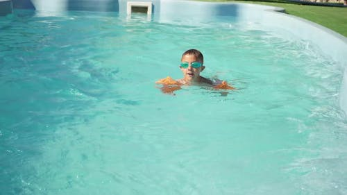 Child Swims in the Pool on a Sunny Summer Day