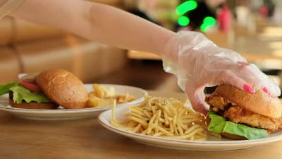 Woman in gloves taking hamburger for eating