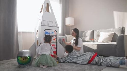 Asian Female with Kids Play in the Living Room at Home a Boy in an Astronaut Costume Lying on the