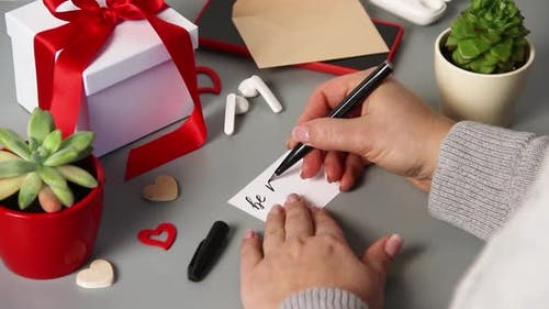 Somebody Writing BE MY VALENTINE card while wrapping valentine's day gift