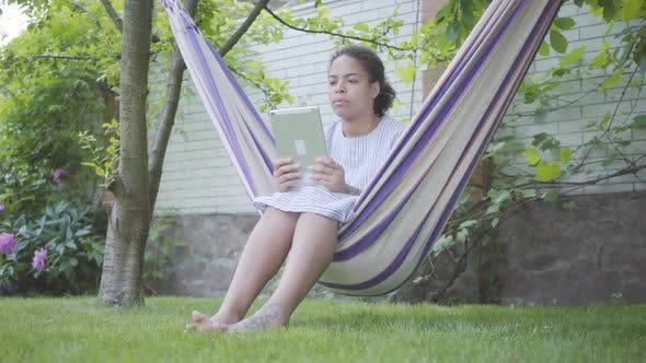 Thumbnail for Portrait Cute Young African American Woman Sitting in the Hammock, Relaxing in the Garden, Texting