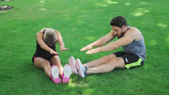 Thumbnail for Young Couple Stretching Before Fitness Workout at Green Grass in Summer Park