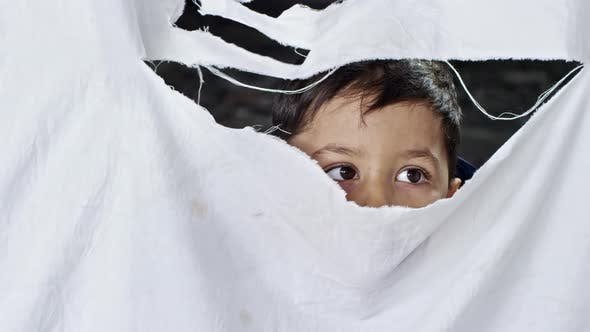 Thumbnail for Refugee Boy Looking through Hole in Cloth