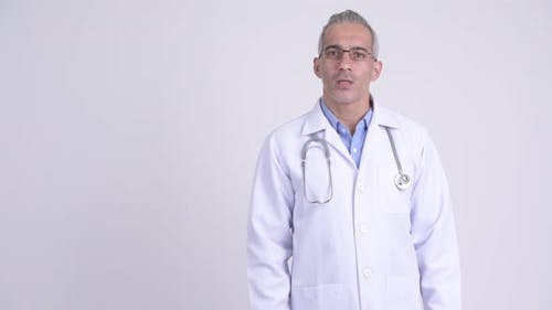 Happy Persian Man Doctor Presenting Something Against White Background