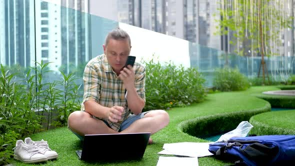 Very Concerned Man Talks with Smartphone Look for Information in Papers Documents Use Tablet PC