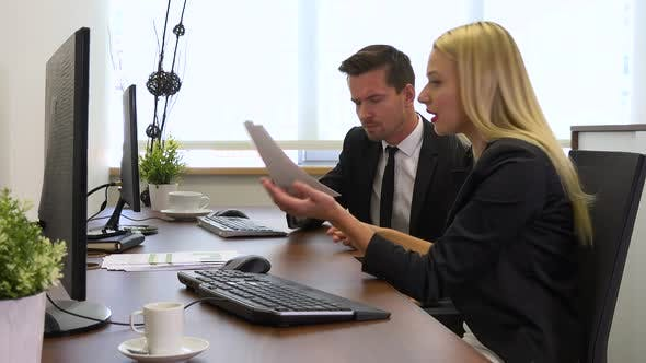 Thumbnail for Two Office Workers, Man and Woman, Sit at Desks with Computers and Argue About Papers