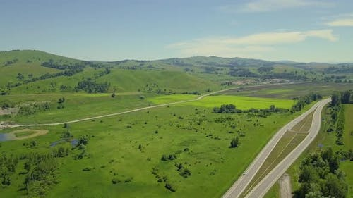 Aerial: Flying Over the Mountainous Terrain and Automobile Route