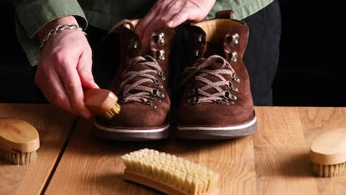 Man's hand clean suede shoes, boots with a brush on wooden background