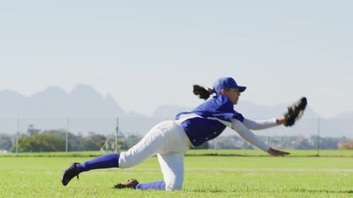 Caucasian female baseball player, fielder catching and diving with ball on baseball field