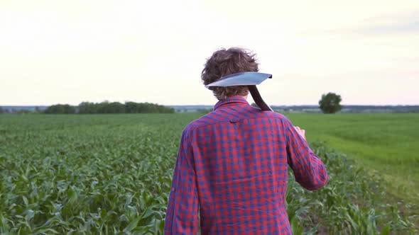 Thumbnail for The Agronomist Walks Through a Corn Field with a Shovel at Sunset