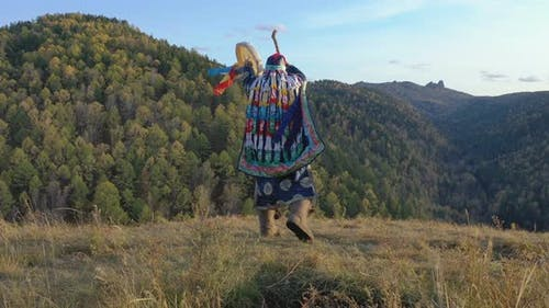 Energetic Dance of an Old Shaman with a Tambourine on the Background of Autumn Mountain Landscape