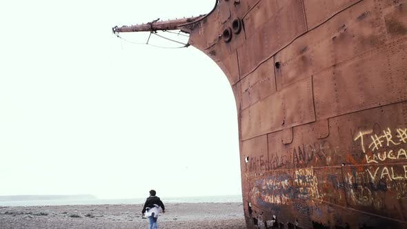 Thumbnail for Boy Running on the Beach next to a Rusty Shipwreck.