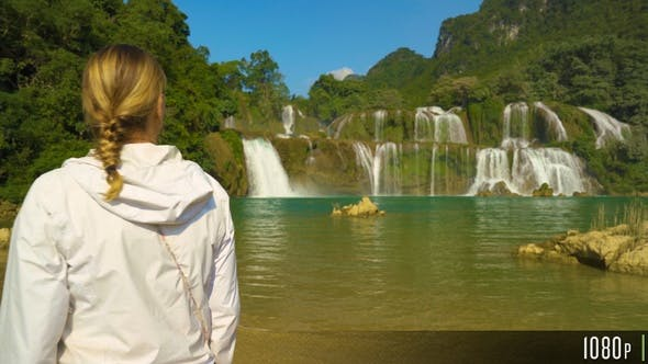 Cover Image for Female Tourist Walking in Front of the Ban Gioc Waterfall Vietnam