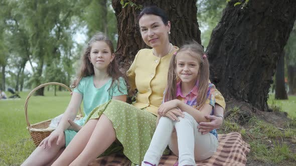 Thumbnail for Mature Woman Sitting on the Grass Under the Tree in the Park with Two Cute Granddaughters
