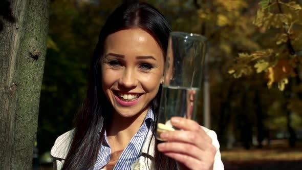 Thumbnail for Slowmotion Young Beautiful Happy Woman Stands in Woods and Shows a Glass with Water