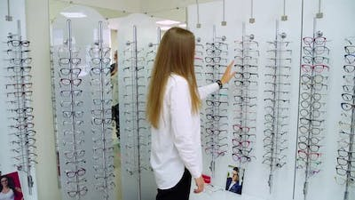 Woman in optical shop. Young woman in optical shop trying eyeglasses